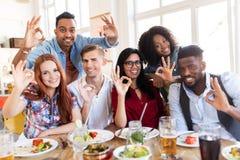 Les amis heureux montrant la main correcte signent au restaurant Photos stock
