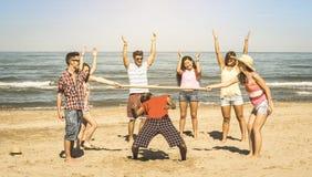 Les amis heureux multiraciaux groupent avoir l'amusement avec le vide à la plage Photos stock