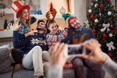 Les amis heureux prennent des photos de Noël à un téléphone Photographie stock libre de droits