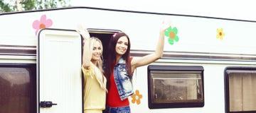 Les amis heureux profitent d'un agréable moment ensemble dans la remorque de campeur Images stock