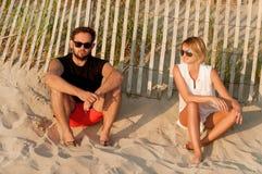 Les amis heureux s'asseyant sur la plage apprécient le coucher du soleil et l'atmosphère romantique Photo libre de droits