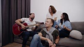 Les amis heureux s'asseyent autour sur le sofa et écoutent le type jouant la guitare acoustique Réunissez-vous pour profiter d'un clips vidéos