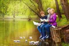 Les amis heureux s'asseyent près de l'étang mettant les bateaux de papier Photos libres de droits