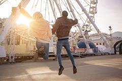 Les amis heureux sautent sur la rue Photographie stock libre de droits