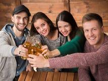 Les amis heureux se reposant avec de l'alcool boit en café Image libre de droits