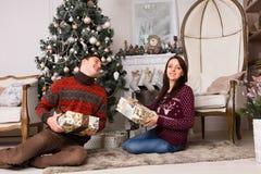 Les amis heureux tenant des cadeaux s'approchent de l'arbre de Noël Images libres de droits