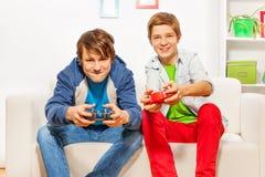 Les amis heureux tiennent des manettes et jouent la console de jeu Image libre de droits