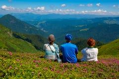 Les amis heureux, voyageurs détendent sur le pré vert de montagne Image libre de droits