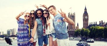 Les amis hippies de sourire avec le selfie collent à Londres Photographie stock