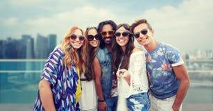Les amis hippies heureux avec le selfie collent au-dessus de la ville Photos stock