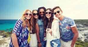 Les amis hippies heureux avec le selfie collent sur la plage Photographie stock libre de droits