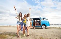 Les amis hippies s'approchent de la voiture de monospace montrant le signe de paix Photographie stock libre de droits
