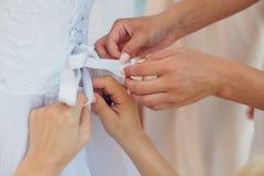 Les amis intimes de la jeune mariée aide sa robe Image libre de droits