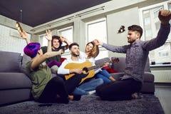 Les amis jouant la guitare, chantent l'amusement à l'intérieur Photos libres de droits