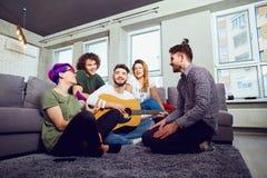 Les amis jouant la guitare, chantent l'amusement à l'intérieur Photographie stock