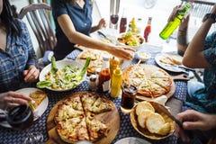 Les amis mangeant de la pizza font la fête ensemble le concept Images libres de droits