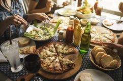 Les amis mangeant de la pizza font la fête ensemble le concept Photo libre de droits