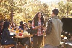 Les amis mangent à la table et à l'entretien deux par le gril à un barbecue Image libre de droits
