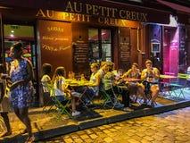 Les amis mangent au café de trottoir dans la lumière jaune de la soirée sur Montmartre à Paris, France Photos libres de droits