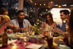 Les amis mangent et parlent à un dîner sur un patio, se ferment  Photo stock