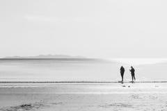 Les amis marchant en mer échouent l'humeur d'amitié Images stock
