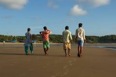 Les amis marchent le long de la plage Leurs traces de congé de pieds sur le sable Flotteur blanc de nuages sur le ciel bleu Photos stock