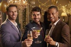 Les amis masculins célébrant à la partie font le pain grillé à l'appareil-photo Photographie stock libre de droits