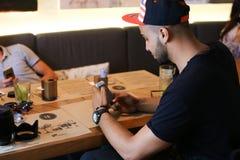 Les amis masculins dans l'entretien de café discutent avec le comprimé de téléphone de technologie Image libre de droits