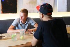 Les amis masculins dans l'entretien de café discutent avec le comprimé de téléphone de technologie Photographie stock