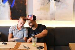 Les amis masculins dans l'entretien de café discutent avec le comprimé de téléphone de technologie Photographie stock libre de droits