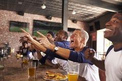 Les amis masculins dans le jeu de montre de barre de sports et célèbrent images stock