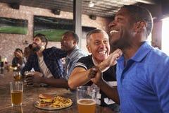 Les amis masculins dans le jeu de montre de barre de sports et célèbrent photo stock