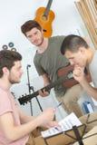 Les amis masculins jouant la guitare acoustique et chantent à la maison Photos stock