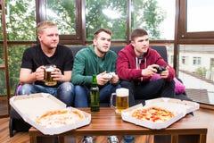 Les amis masculins jouant les jeux vidéo, la bière de boissons et ont l'amusement à la maison Photo stock