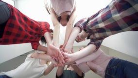Les amis mettent leurs mains sur l'un l'autre et les ouvrent, la jeunesse avec des émotions heureuses s'élèvent tous en cercle et clips vidéos