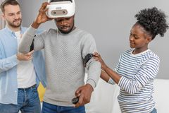 Les amis multiculturels aident le type africain au manade avec le casque de vr pendant le temps de poing photos stock