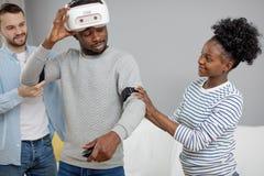 Les amis multiculturels aident le type africain au manade avec le casque de vr pendant le temps de poing image libre de droits