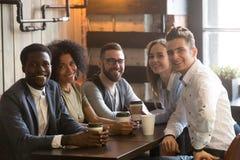 Les amis multiraciaux groupent regarder l'appareil-photo se reposant en café, por Photos libres de droits