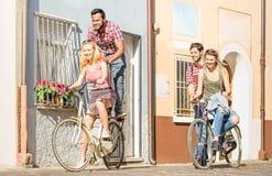 Les amis multiraciaux heureux couplent avoir la bicyclette d'équitation d'amusement Image stock