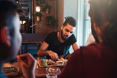 Les amis multiraciaux mangent le petit déjeuner dans la barre de salon Les jeunes hommes causent tout en ayant la nourriture et l Photos libres de droits