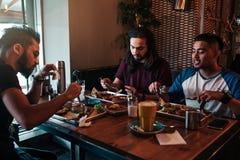 Les amis multiraciaux mangent le petit déjeuner en café Les jeunes hommes causent tout en ayant la nourriture et les boissons sav Images libres de droits