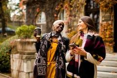 Les amis multiraciaux marchant autour de la ville, parlant et portent c Photos stock
