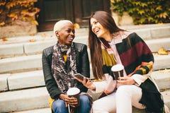 Les amis multiraciaux s'asseyant en parc d'automne, parlant et portent la Co Photographie stock libre de droits