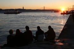 Les amis observent le coucher du soleil Photographie stock