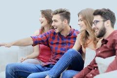 Les amis observent votre exposition préférée se reposer sur le divan Photographie stock