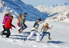 Les amis ont l'amusement à l'hiver sur la neige fraîche Photos stock