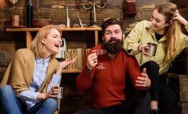 Les amis ont l'amusement, parlant et buvant dans l'intérieur en bois Homme et dames sur les visages heureux discutant et buvant Images libres de droits