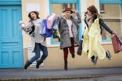 Les amis ont satisfait sauter sur la rue après l'achat Images stock