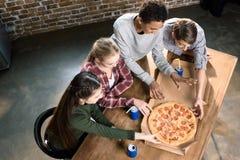 Les amis passant le temps ainsi que la pizza et la soude boit, mangeant le concept de pizza à la maison Images stock