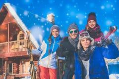 Les amis passent des vacances d'hiver au cottage de montagne Images libres de droits